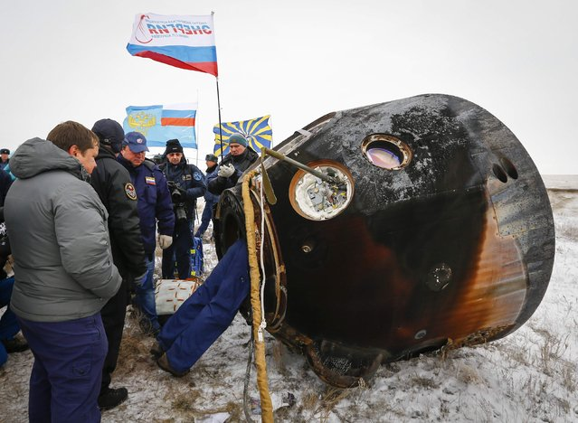 Ground personnel work next to the Soyuz TMA-13M capsule of the International Space Station (ISS) crew of Alexander Gerst of Germany, Maxim Suraev of Russia and Reid Wiseman of the U.S. after its landing near the town of Arkalyk in northern Kazakhstan November 10, 2014. (Photo by Shamil Zhumatov/Reuters)