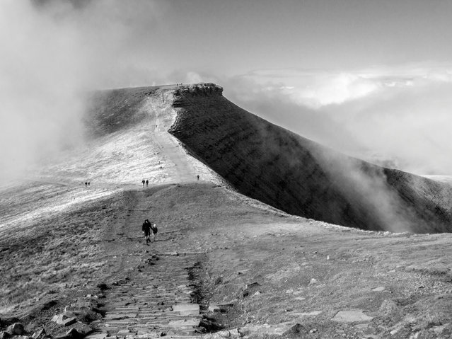 """""""During a family hike in the Brecon Beacons, south Wales, clear skies gave way to swirling cloud over Pen y Fan and Corn Du summits. Shaded hillside contrasted nicely with the clouds, ideal conditions for a black and white photograph"""". (Photo by Andrew Gilmore/The Guardian)"""