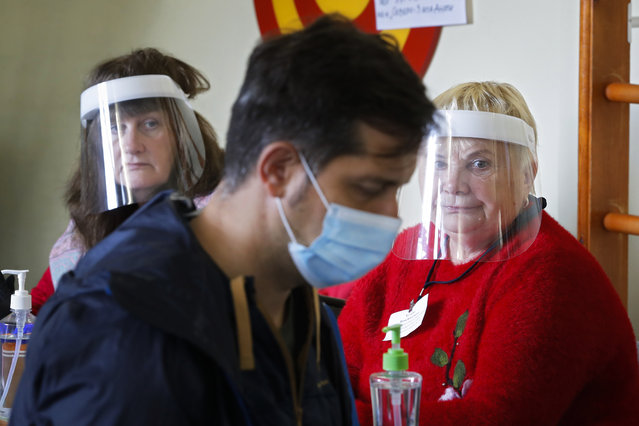 Members of the election commission wearing face masks to protect against coronavirus infection, look at a voterat a poling station during Leningrad region's governor and municipal elections in Luppolovo village, outside St. Petersburg, Russia, Sunday, September 13, 2020. (Photo by Dmitri Lovetsky/AP Photo)