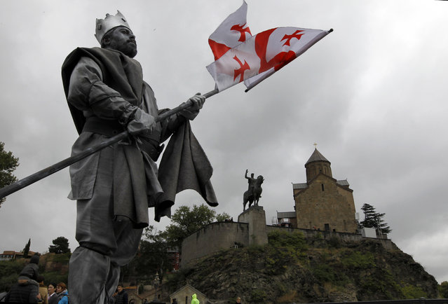 """An actor dressed as Vakhtang I """"Gorgasali,"""" a king of Iberia, holds a Georgian national flag in front of the Metekhi Church and a monument to Vakhtang I """"Gorgasali,"""" during the annual Tbilisoba City Day celebration in Tbilisi, Georgia, Saturday, October 17, 2015. Tbilisoba is an annual October festival, celebrating the diversity and history of Tbilisi, the capital of Georgia. (Photo by Shakh Aivazov/AP Photo)"""
