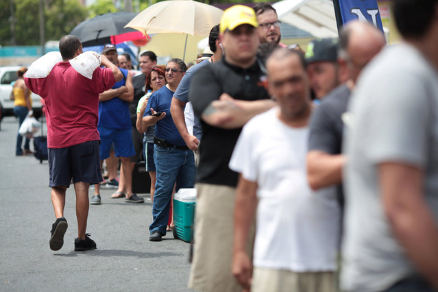 People stand in line to buy ice during a power outage after a fire at an energy plant knocked out electricity for the bulk of the island, in San Juan, Puerto Rico, September 22, 2016. (Photo by Alvin Baez/Reuters)