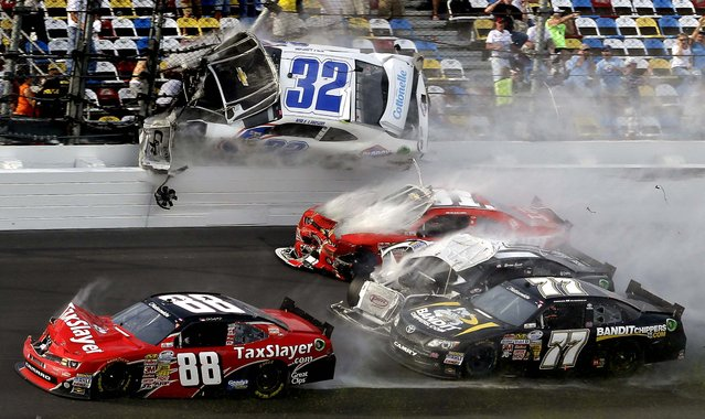 Kyle Larson (32) goes airborne into the catch fence in a multi-car crash including  Dale Earnhardt Jr. (88), Parker Kilgerman (77), Justin Allgaier (31) and Brian Scott (2) during the final lap of  the NASCAR Nationwide Series race at Daytona International Speedway, on February 23, 2013. (Photo by John Raoux/Associated Press)