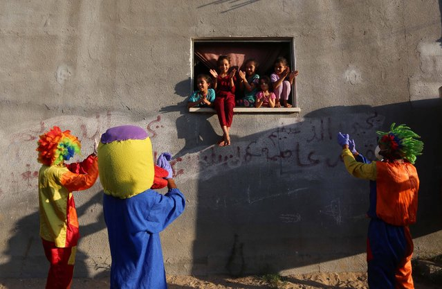 Palestinian youth, wearing clown costumes, entertain children on September 02, 2020 in Gaza City, Gaza during the lockdown imposed as a measure against the coronavirus (COVID-19) pandemic. (Photo by Ashraf Amra/Anadolu Agency via Getty Images)