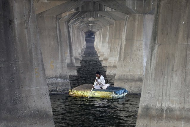A fisherman rows a raft under a bridge in the Sabarmati River, in the western Indian city of Ahmedabad, November 25, 2014. (Photo by Amit Dave/Reuters)