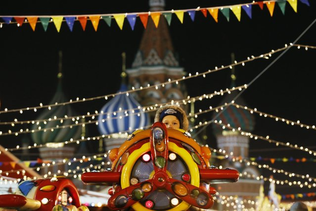 A child sits in an amusement ride on the first day of a fair organized by GUM departmental store for the upcoming Christmas and New Year celebrations at Moscow's Red Square, November 29, 2014. (Photo by Maxim Zmeyev/Reuters)