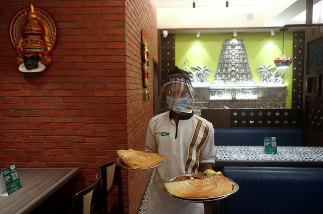 A waiter wearing a protective mask and face shield carries food on trays at a restaurant after it reopened amidst the spread of the coronavirus disease (COVID-19), in Mumbai, India, October, 5, 2020. (Photo by Francis Mascarenhas/Reuters)