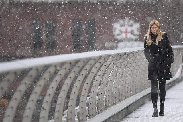 A commuter crosses Millennium Bridge in London as heavy snow falls over the capital Monday February 2018.  Freezing temperatures and heavy snow is predicted to settle over much of Britain, and expected to effect Europe into the week ahead. (Photo by Victoria Jones/PA Wire via AP Photo)