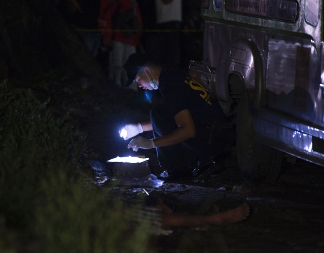 "A member of police Scene of the Crime Operative (SOCO) look for evidence next to a dead suspected drug pusher killed during a drug buy-bust operation by police along a rail line in Caloocan City suburban Manila on early September 30, 2016. Philippine President Rodrigo Duterte on September 30 drew a parallel with his deadly crime war and Hitler's massacre of Jews, as he said he was ""happy to slaughter"" millions of drug addicts. (Photo by Ted Aljibe/AFP Photo)"