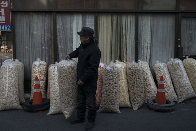 A man sells large bags of popped grains at the traditional market in Gangneung, South Korea, Tuesday, February 13, 2018. Markets like this one are a common sight in South Korea. And while the Pyeongchang promoters are hoping it will impress the foreign tourists here for the games, it hasn't been given much of an Olympic makeover. (Photo by Felipe Dana/AP Photo)