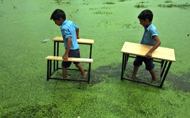 Primary school boys carry their benches after their school was flooded due to heavy rains at Bassi Kalan village in the outskirts of Jammu, Kashmir, on August 10, 2011. (Photo by Mukesh Gupta/Reuters)