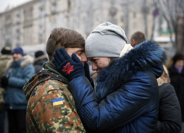"A woman embraces her boyfriend from ""Kiev 12"" military defence battalion before a welcoming ceremony in central Ukrainian capital Kiev December 6, 2014. (Photo by Gleb Garanich/Reuters)"