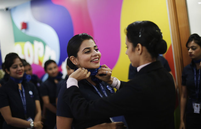 An instructor adjusts the neck scarf of a prospective flight attendant during their training session at the Indigo Airlines' Ifly training centre in Gurgaon on the outskirts of New Delhi November 18, 2014. (Photo by Adnan Abidi/Reuters)