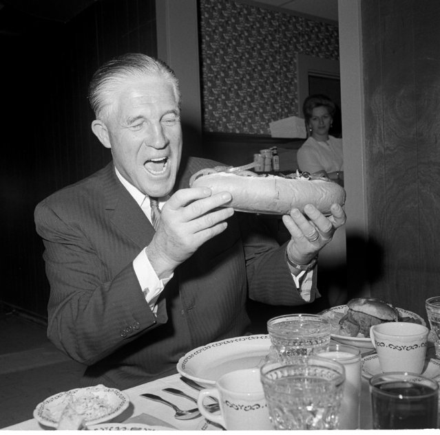 Michigan Gov. George Romney gets ready to bite into a submarine sandwich at Concord, N.H., during a luncheon stop in his campaign tour of the Granite State, February 22, 1968.  Romney is campaigning for first-in-nation presidential primary. (Photo by Bill Chaplis/AP Photo)
