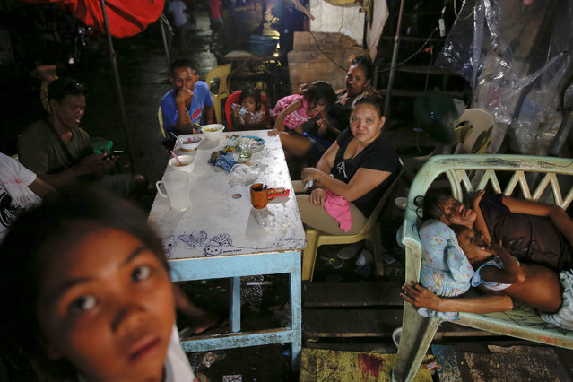 The wife and daughter of a man who was killed during a drug buy-bust operation sleep as relatives and friends gather to mourn outside his home in Manila, Philippines October 9, 2016. (Photo by Damir Sagolj/Reuters)