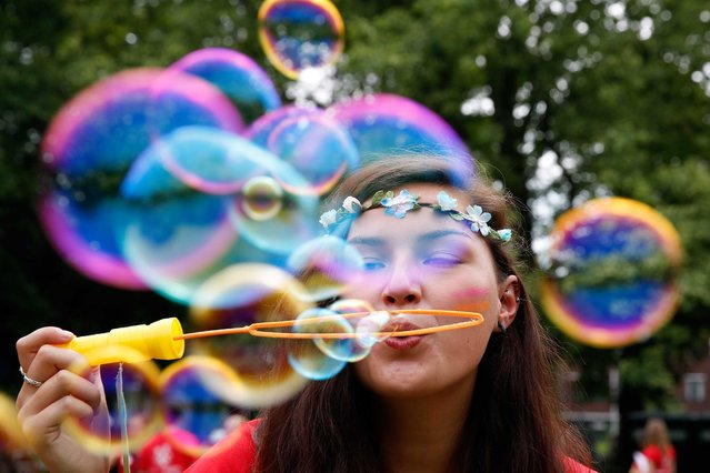 A student blows bubbles on the first day of the university introduction days for students in the Wilhelminapark in Utrecht, the Netherlands, 10 August 2015. First year students attend introduction days ahead of their studies.  (Photo by Bas Czerwinski/EPA)