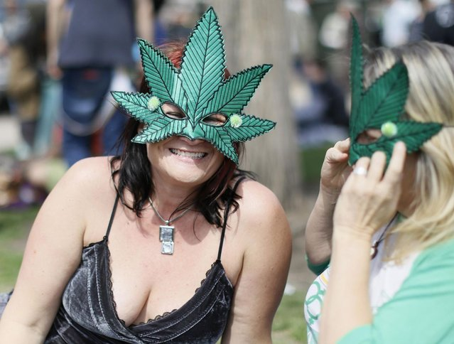 Women wearing marijuana leaf masks smile at the 4/20 marijuana holiday in Civic Center Park in downtown Denver April 20, 2013. Thousands of marijuana enthusiasts gathered in Denver on Saturday for an annual weekend celebration of cannabis, the first such assemblage since Colorado voters legalized the recreational use of pot last fall. (Photo by Rick Wilking/Reuters)