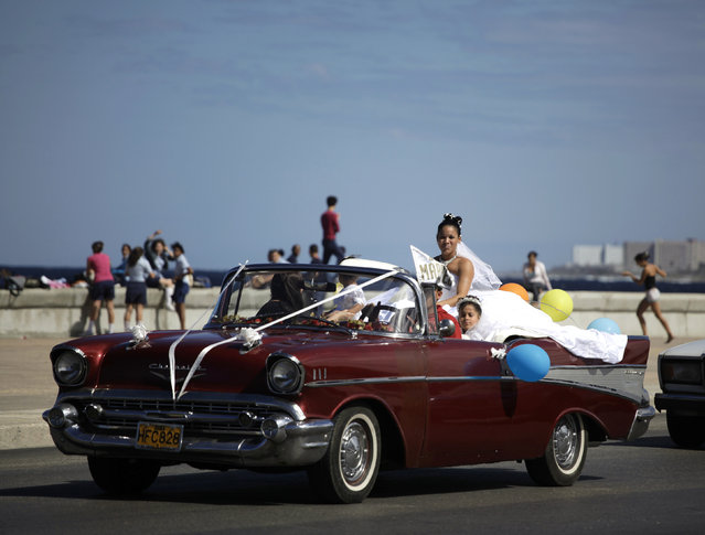 A Cuban bride rides in a vintage car along Havana's seafront boulevard, January 26, 2010. (Photo by Desmond Boylan/Reuters)