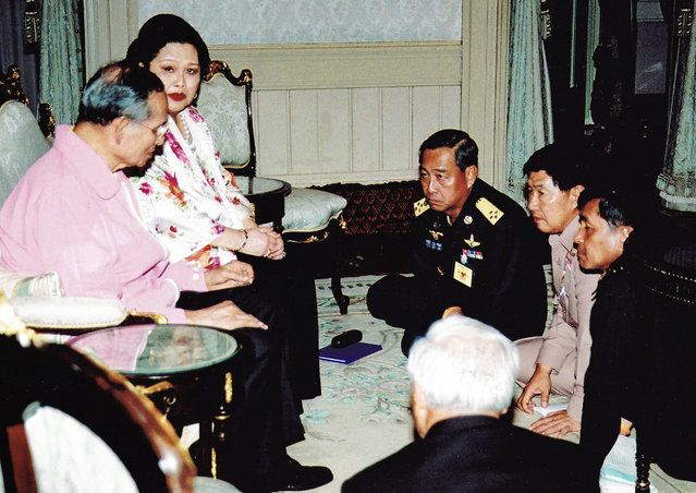 Thai King Bhumibol Adulyadej (L) and Queen Sirikit meet with Thailand's military coup leaders in Bangkok on September 19, 2006. Coup leaders sitting are (L-R) Air Forces Chief Chalit Phukpasuk, Navy Chief Admiral Satiraphan Kayanont and Army Chief General Sonthi Boonyaratglin. (Photo by Reuters)