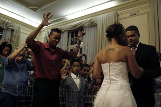 Guests take part in a group wedding celebrated by an evangelical pastor in Rio de Janeiro December 17, 2014. (Photo by Pilar Olivares/Reuters)