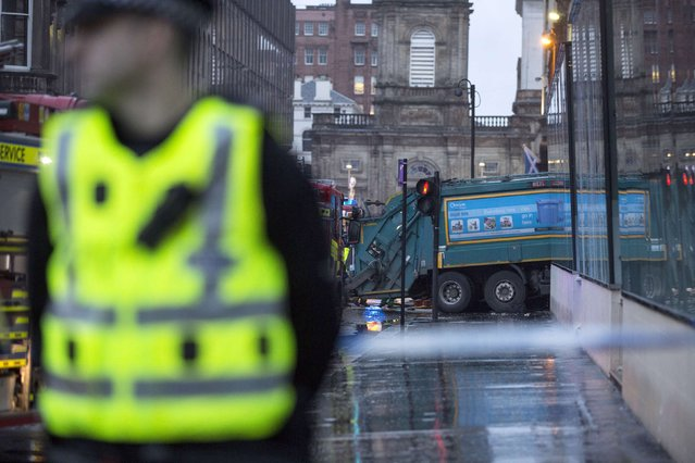 A policeman stands near a refuse truck that crashed into pedestrians in George Square, Glasgow, in Scotland December 22, 2014. (Photo by Reuters/Stringer)