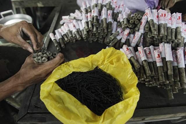 A worker makes firecrackers at a makeshift factory in Bocaue town, Bulacan province, north of Manila December 27, 2014. (Photo by Romeo Ranoco/Reuters)