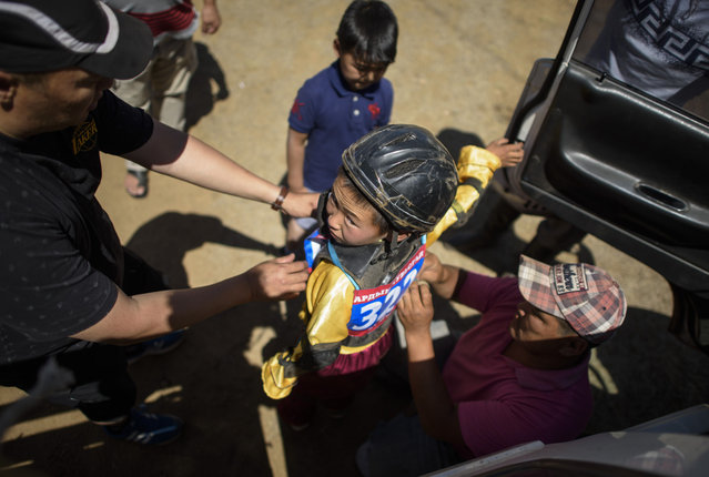 This picture taken on July 11, 2015 shows 13-year-old jockey Purevsurengiin Togtokhsuren (C) being fitted into his racing uniform to compete in the 'Inkhnas' (over five-year-old horses) horse race during the Naadam in Khui Doloon Khudag, some 50 kms west of Ulan Bator. (Photo by Johannes Eisele/AFP Photo)