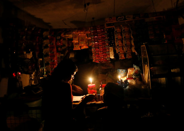 A customer waits to buy food from a shop during a power cut in Kesbewa, Sri Lanka, October 18, 2016. (Photo by Dinuka Liyanawatte/Reuters)