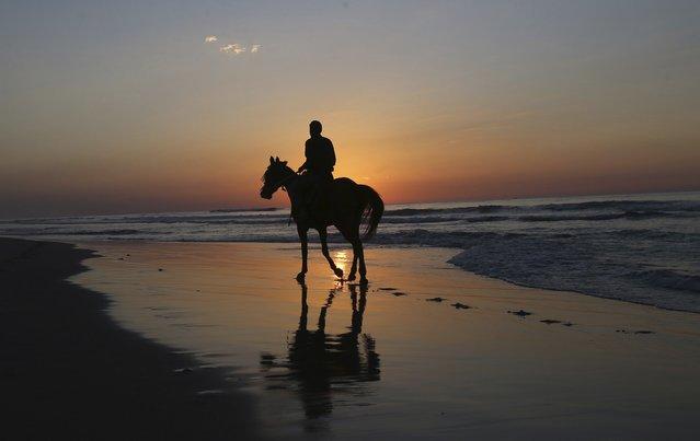 A Palestinian rides a horse on Gaza beach at the Mediterranean sea during sunset December 31, 2014. (Photo by Ibraheem Abu Mustafa/Reuters)
