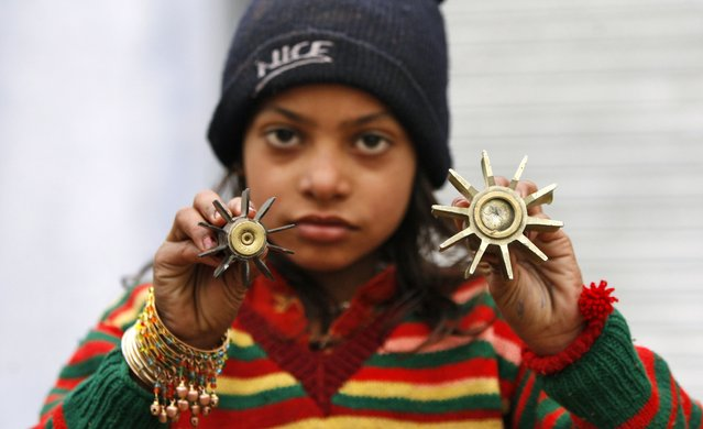 An Indian border girl displays a mortar shell allegedly fired from the Pakistan side of the border at Bainglad village in Samba sector, about 52 kilometers (32 miles) from Jammu, India, Tuesday, January 6, 2015. Pakistani troops fired gunshots and mortar shells that killed an Indian soldier in northern Kashmir on Monday after a lull in the countries' cross-border firing, an Indian paramilitary official said. Pakistan blamed India for the violence and said two civilians were killed by Indian shelling. (Photo by Channi Anand/AP Photo)