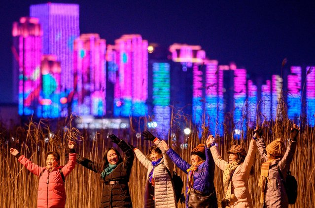 People pose for pictures on the banks of Yangtze River on New Year's Eve in Wuhan, in China's central Hubei province on December 31, 2020. (Photo by Noel Celis/AFP Photo)