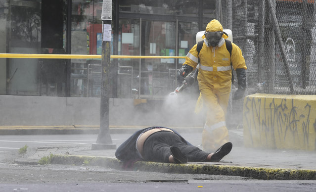 A worker from the city's forensic department sprays disinfectant over the body of a woman who died on a street in Quito, Ecuador, Thursday, May 14, 2020. Forensic workers at the scene conducted a COVID-19 rapid test and said the woman tested negative. (Photo by Dolores Ochoa/AP Photo)