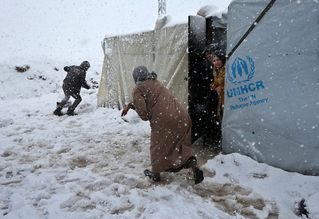 Syrians throw snow at each other at a refugee camp in Deir Zannoun village, in the Bekaa valley, east Lebanon, Wednesday, January 7, 2015. While the storm disrupted life for everyone, it proved particularly trying for the hundreds of thousands of Syrian refugees who live in tents and makeshift shelters in the Bekaa. (Photo by Hussein Malla/AP Photo)