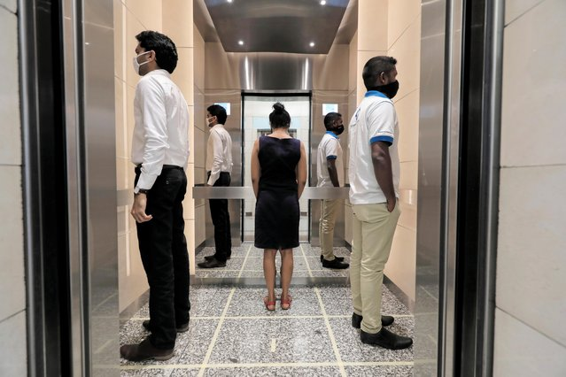 People practice social distancing inside an elevator prior to arriving to their work places at World Trade Center, after the government announced that private and state companies will reopen their offices after almost two months of lockdown amidst concerns about the spread of coronavirus disease (COVID-19) in Colombo, Sri Lanka on May 11, 2020. (Photo by Dinuka Liyanawatte/Reuters)