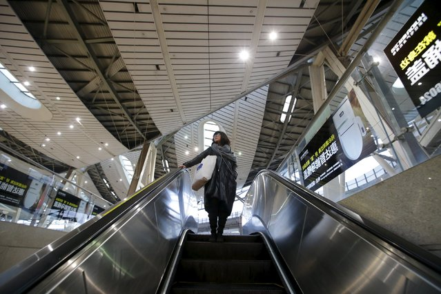Li Nan, a makeup artist, takes an escalator on her commute into Beijing for work from Tianjin, China, November 18, 2015. (Photo by Jason Lee/Reuters)
