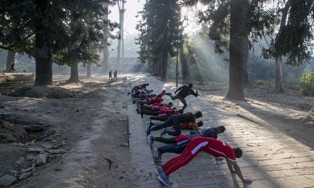 A Nepalese physical fitness trainer kicks a student as a form of punishment while they work out at a forest area near Pashupatinath Temple in Kathmandu, Nepal, Monday, January 11, 2021. (Photo by Niranjan Shrestha/AP Photo)