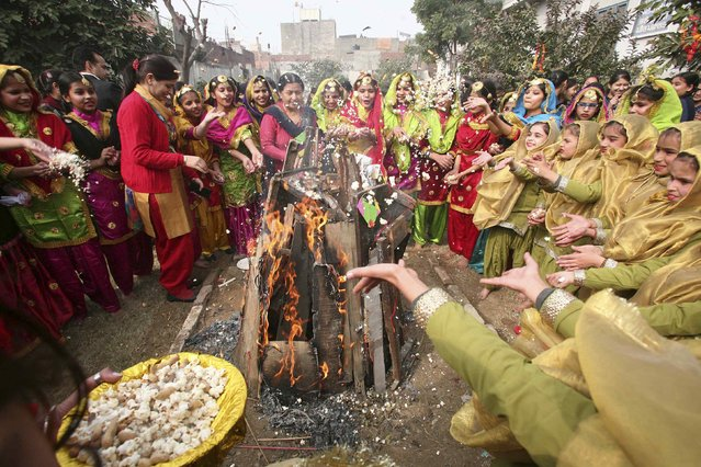 Schoolgirls wearing colourful dresses cheer around a bonfire during the Lohri festival celebrations at their school in the northern Indian city of Amritsar January 12, 2015. (Photo by Munish Sharma/Reuters)