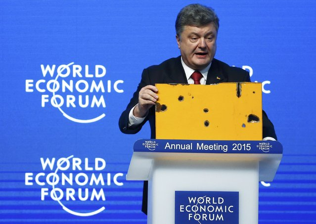 Ukrainian President Petro Poroshenko holds a fragment of a bus body which he says shows a Russian missile attack on a civilian bus as he addresses The Future of Ukraine event in the Swiss mountain resort of Davos January 21, 2015. (Photo by Ruben Sprich/Reuters)