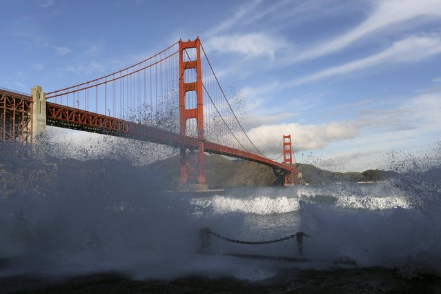 Waves crash against a sea wall in San Francisco Bay beneath the Golden Gate Bridge in San Francisco, California December 16, 2014. A gale warning for offshore winds has been issued through Friday as another round of storms is expected to hit the Bay Area. (Photo by Robert Galbraith/Reuters)