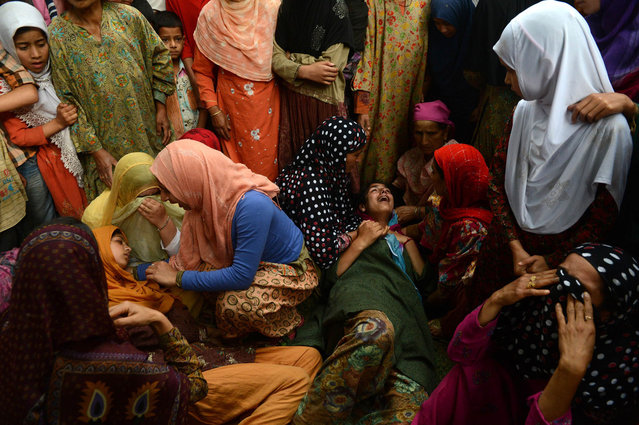 Kashmiri Muslim women mourn during the funeral of Kashmiri rebel Shahnawaz Ahmed alias Tahir Khan, of Hizbul Mujahideen at Tral, some 40kms south of Srinagar on July 2, 2013. Indian troops shot dead three rebels while one special operation group (SOG) soldier died and five injured in a firefight with militants in the restive Himalayan state.  About a dozen armed groups have been fighting Indian forces since 1989 for Kashmir's independence or for its merger with Pakistan. (Photo by Tauseef Mustafa/AFP Photo)