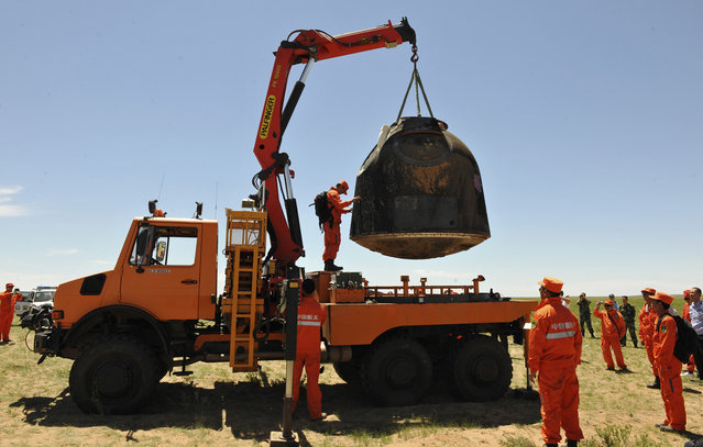 The re-entry capsule of China's Shenzhou-10 spacecraft is loaded onto a truck after it landed at in Inner Mongolia Autonomous Region, on June 26, 2013. (Photo by Reuters/China Daily via The Atlantic)