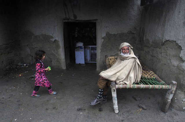 Abdul Karim, 75, covers himself from the cold while sitting on a rope bed near a shop on the outskirts of Peshawar January 22, 2015. (Photo by Fayaz Aziz/Reuters)