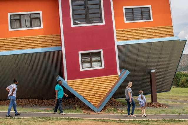 "Tourists walk around the ""Upside down house"" tourist attraction near Johannesburg, South Africa, 04 November 2020. The newly build tourist attraction is a first for South Africa and appears to be a house build upside down and features rooms within the house that are also upside down, creating a unique and mind shifting experience. (Photo by Kim Ludbrook/EPA/EFE)"