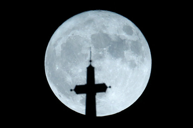 The supermoon is seen behind the cathedral cross in Zagreb, Croatia November 14, 2016. (Photo by Antonio Bronic/Reuters)