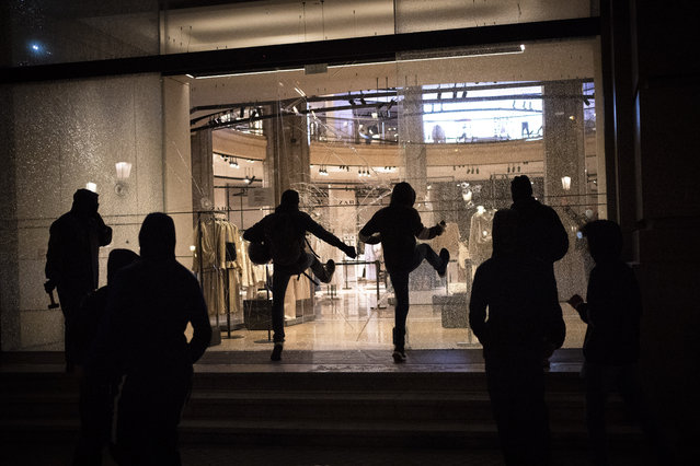 Protesters break the windows of a commerce during clashes following a protest condemning the arrest of rap singer Pablo Hasél in Barcelona, Spain, Saturday, February 27, 2021. (Photo by Emilio Morenatti/AP Photo)