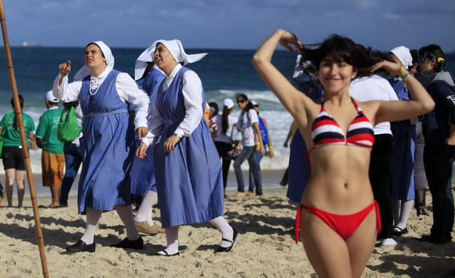 Nuns and sunbathers wait for the arrival of Pope Francis on Copacabana beach in Rio de Janeiro, July 26, 2013. Pope Francis on Thursday issued the first social manifesto of his young pontificate, telling slum dwellers in Brazil that the world's rich must do much more to wipe out vast inequalities between the haves and the have-nots. (Photo by Ricardo Moraes/Reuters)