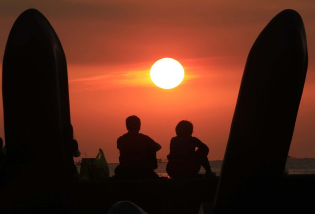 A couple sits on the breakwaters as they watch the sun set along Manila bay in Manila, Philippines February 5, 2015. (Photo by Romeo Ranoco/Reuters)