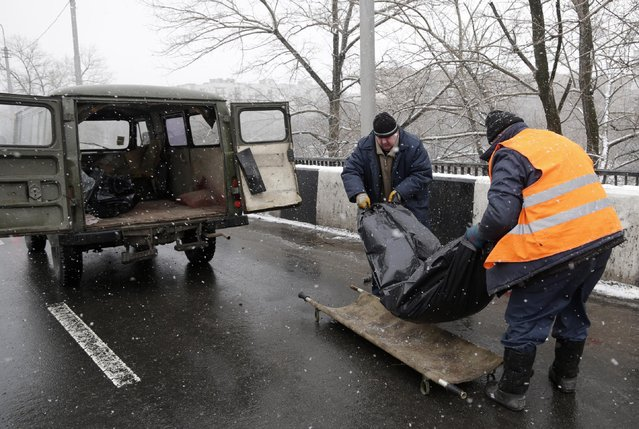 A bag with the body of someone killed in a recent shelling is loaded into a vehicle in Donetsk, Ukraine, Monday, February 9, 2015. (Photo by Petr David Josek/AP Photo)