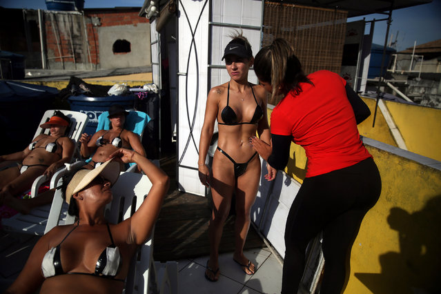"""A woman gets some sunblock from a worker of the Erika Bronze spa before sunbathing on a terrace to have the perfect bikini mark (""""marquinha"""" in Portuguese), in Rio de Janeiro, Brazil, November 21, 2016. (Photo by Pilar Olivares/Reuters)"""