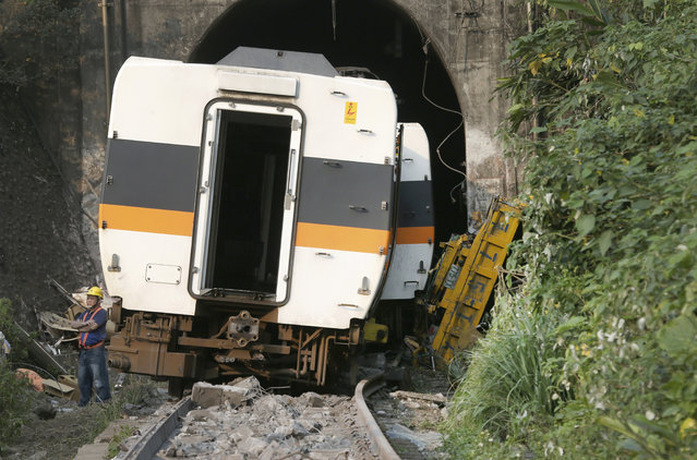 A worker stands in front of the derailed train near Taroko Gorge in Hualien, Taiwan on Saturday, April 3, 2021. The train partially derailed in eastern Taiwan on Friday after colliding with an unmanned vehicle that had rolled down a hill, killing and injuring dozens. (Photo by Chiang Ying-ying/AP Photo)