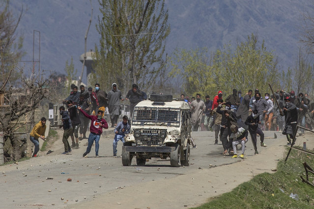 Kashmiri villagers throw stones and bricks at a police vehicle during a protest near the site of a gunbattle in Pulwama, south of Srinagar, Indian controlled Kashmir, Friday, April 2, 2021 (Photo by Dar Yasin/AP Photo)